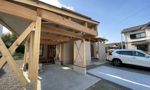 木で組んだガレージが特徴の家